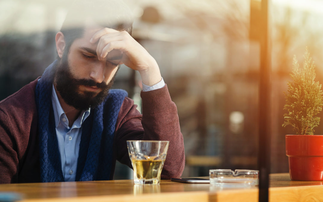 Depressed male drinking alcohol in a bar thinking about cocaine during daytime